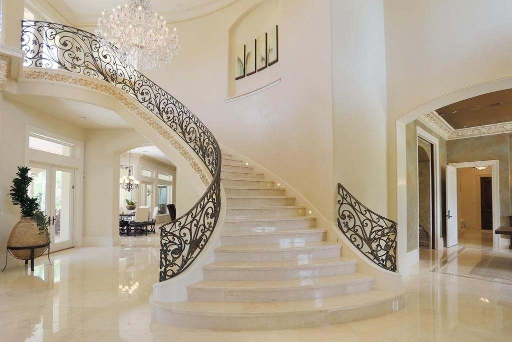Dramatic Scrolling Staircase With Crema Marfil Marble Slab Stairs Crystal Chandelier Large Art Niche Custom Designed Wroug Staircase Design Home Stairs Design