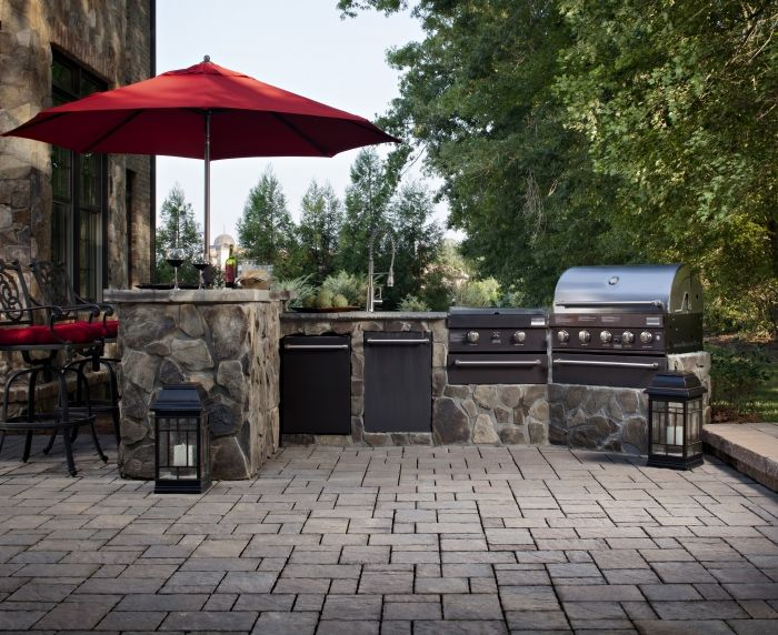 Outdoor Kitchen With Brick Pavers And Stainless Steel Grill
