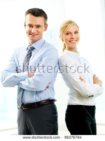 Two business people standing back to back and smiling at camera