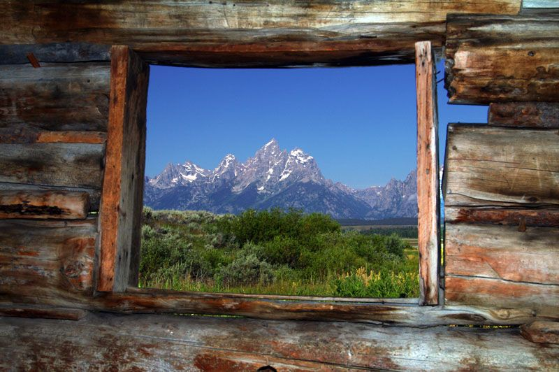 Grand Tetons Framed In Deserted Log Cabin Window