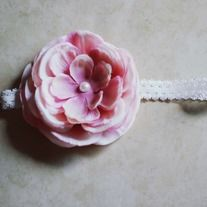 Gorgeous elastic white lace headband with light pink flower. Pearl in center.     Will be sized to fit a baby, child, or woman...let me know what you'd like!