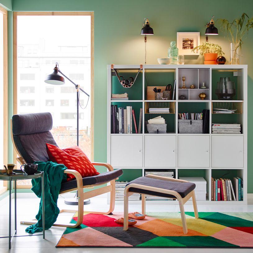 Rincón de lectura en verde y gris con una alfombra multicolor y unas