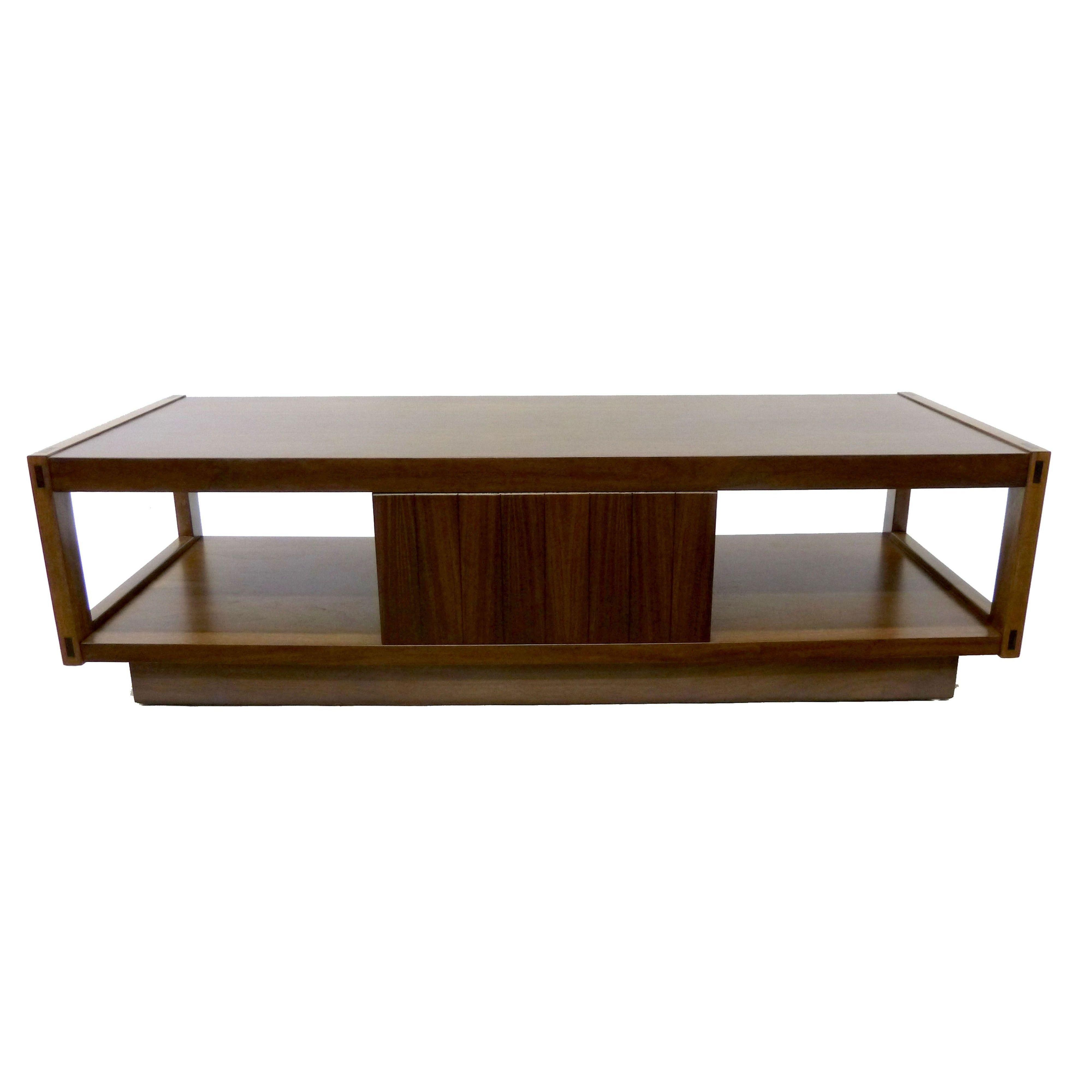 This highly structured, mid-century modern coffee table by Lane is rendered in walnut and brass and features plenty of storage including a large center drawer flanked by two open shelves ideal for the display of magazines and books. The piece's modern lines are juxtaposed with traditional joinery at the corners highlighted by lighter shades of walnut. The coffee table rests on an inverted base also in walnut. Lane logo is branded inside drawer.