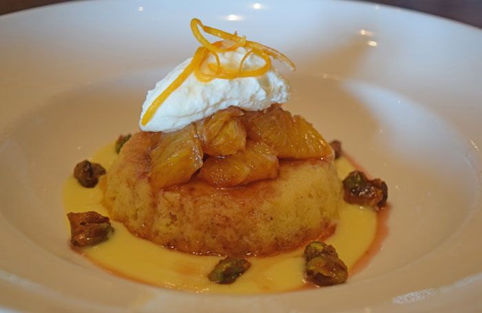 Coconut-Tahini Cake with pomegranate and honey marinated oranges, candied pistachios, crème anglaise and whipped cream // Green Valley Grill Menu - Greensboro NC