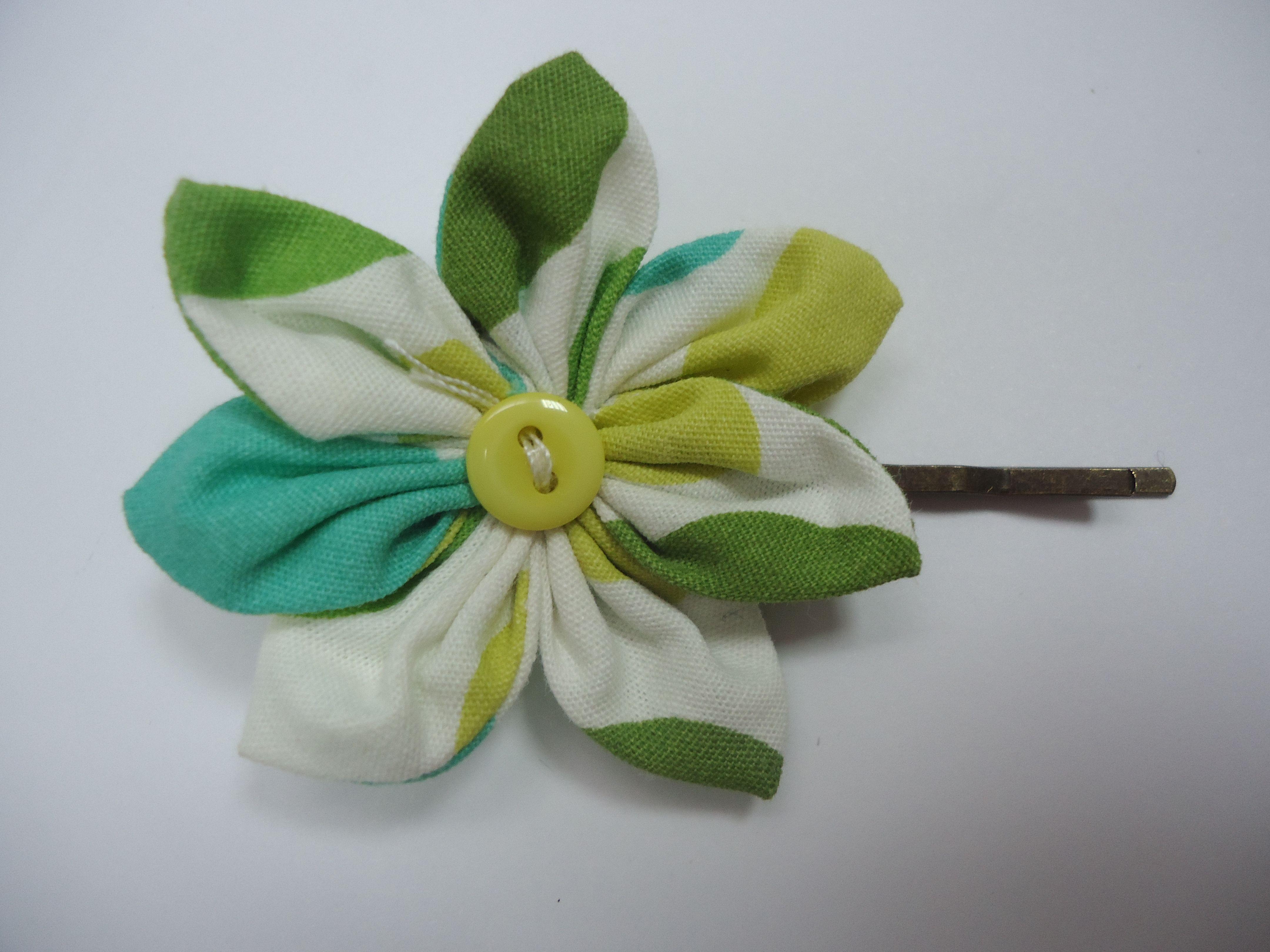 Jolie barrette en coton dans les tons noir, vert, jaune et blanc, en forme de fleur, avec un coeur en bouton jaune. La barrette est une pince bronze de 5 cm.  Tarifs : 4€ + fdp