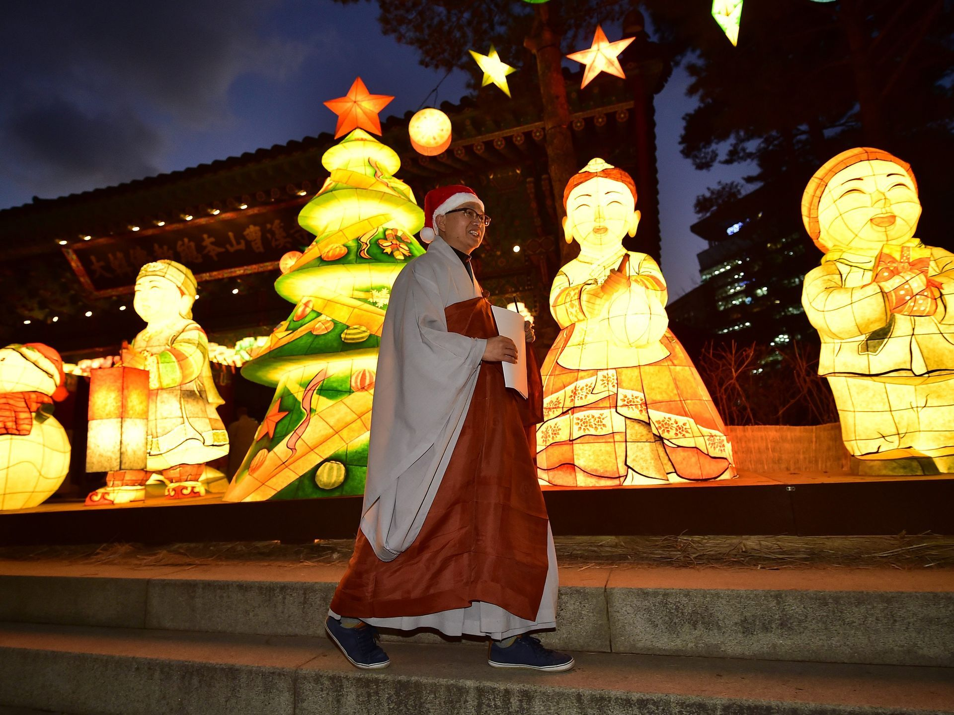 a buddhist monk wearing a santa hat walks past a christmas tree during a lighting ceremony at the main gate of jogye temple in seoul
