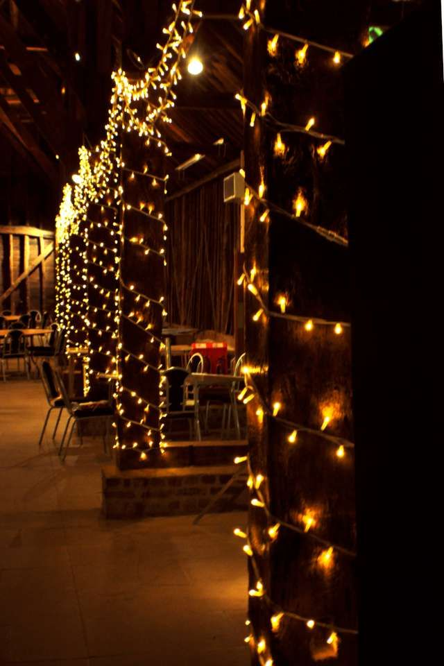 Looking down the barn, fairy lights wound around the pillars for wedding  sparkle | Wedding lights, Fairy lights wedding, Pavilion wedding reception