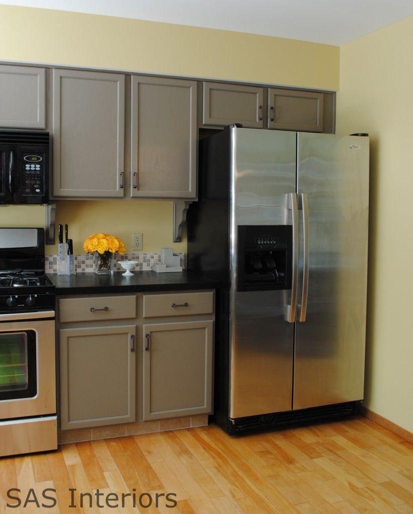 beautiful taupe kitchen cabinet with black countertop and cahrm