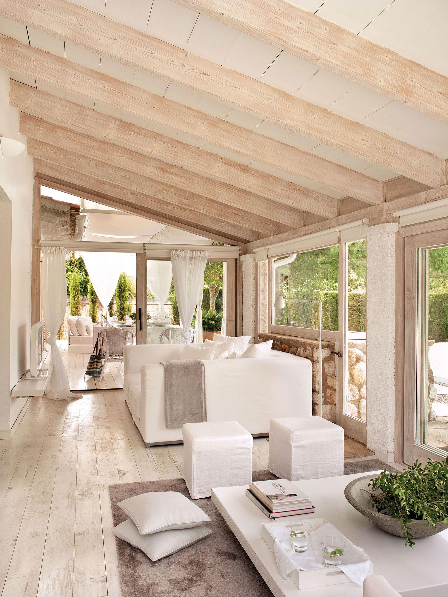 Salón actual en blanco con grandes cristaleras al jardín, suelo de ...
