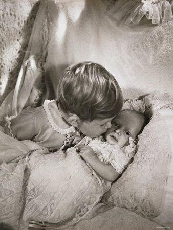 Prince Charles kisses 1 month old baby Princess Anne, 1950