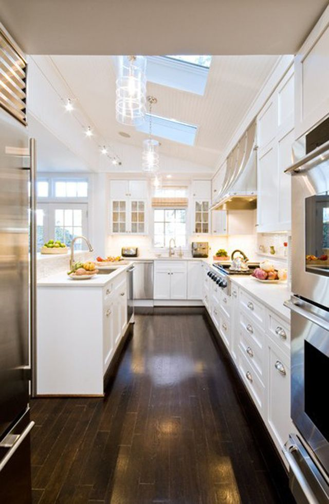 white kitchen with dark flooring, so chic
