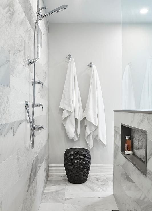 Polished Nickel Towel Hooks Are Mounted Above A Woven Black Stool On A Wall Adjacent To An Open Shower Fitted With An Exposed Plumbing Pol Open Showers