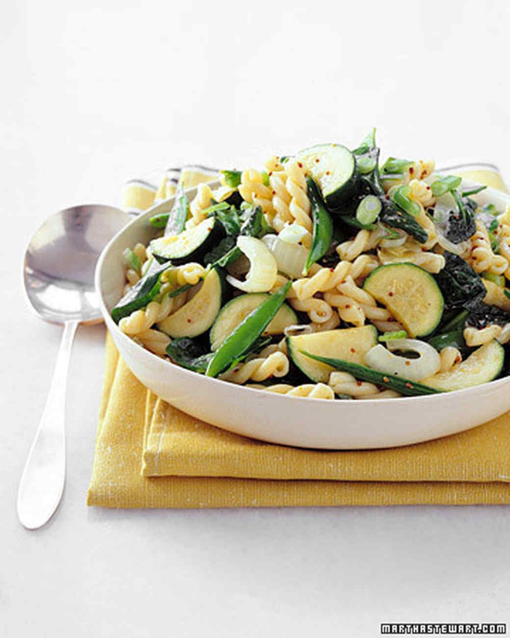 A medley of greens -- zucchini, snap peas, baby spinach, scallions -- combines with a simple mustard vinaigrette to create this appealing pasta salad.