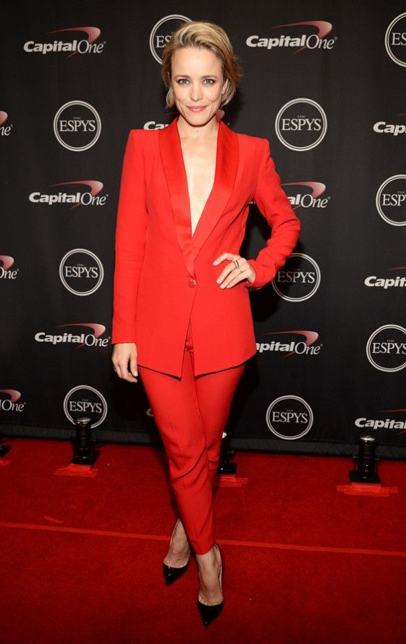 Rachel McAdams wears a red blazer and pant suit with black pointed toe heels.