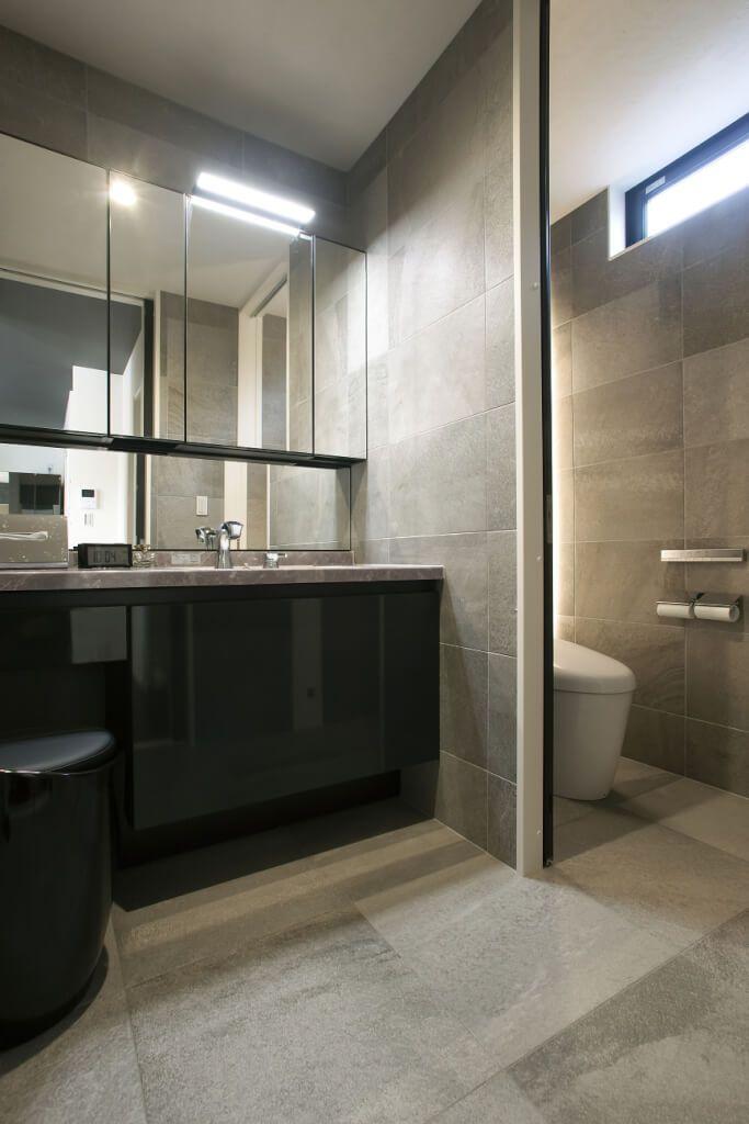 まるで海外のホテルに来たかのような洗練された洗面台は グレーと黒のモノトーンで統一しています 床と壁はキッチンと同じタイルを使用 生活感を感じさせない仕上がりに ミラーの裏が棚になっているので 散らかりがちな小物やリネン類もすっきりと収納することができ