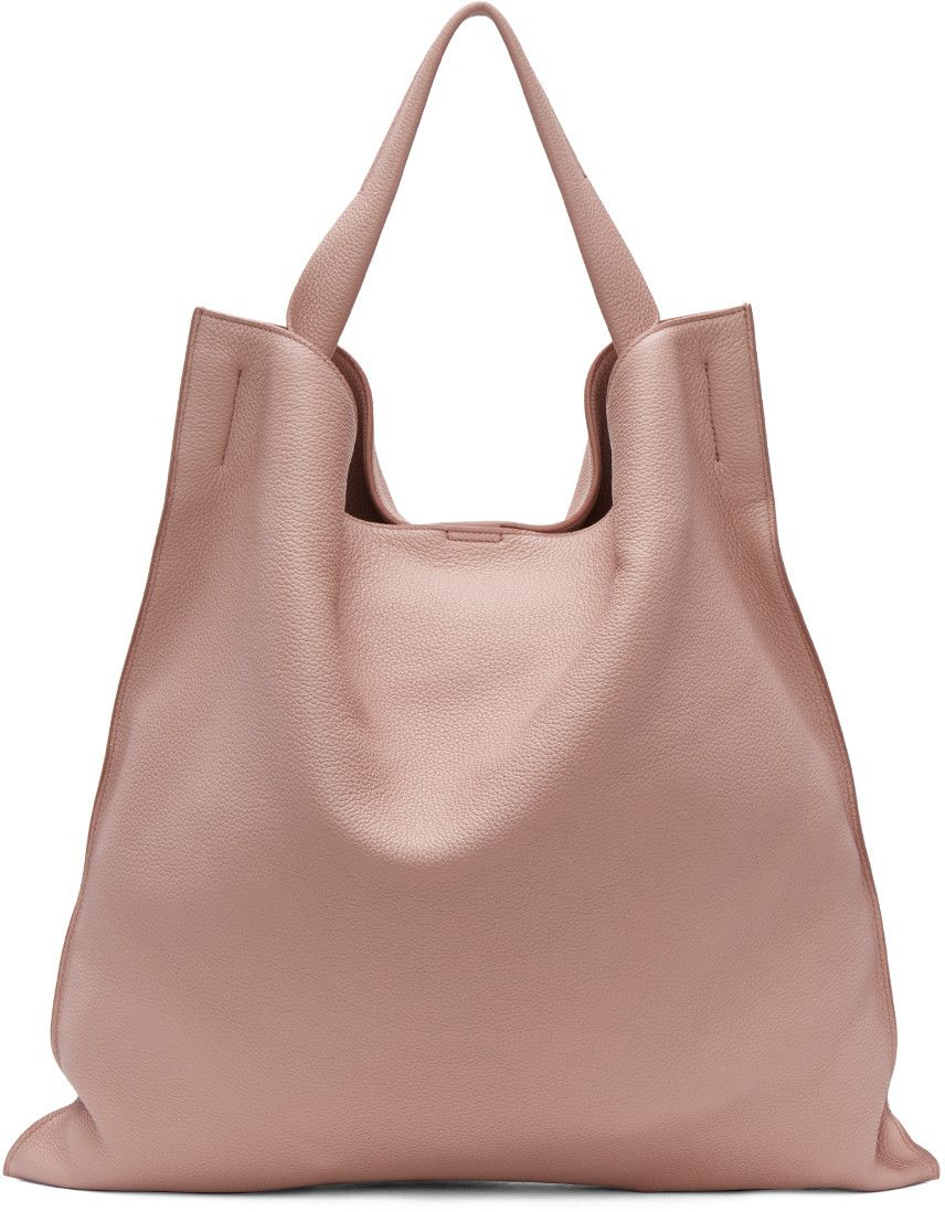 b2e01b37271d Grained calfskin tote in light pink. Carry handle at top. Logo embossed at  face. Magnetic press-stud fastening at throat. Patch pocket at interior.