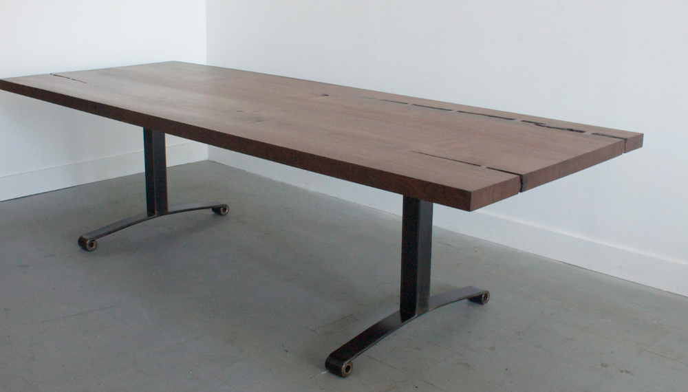 """The FDNY base Slab Dining Table is created from a one of a kind hardwood slab set on a  3"""" X 3"""" steel column and a reclaimed leaf spring. Each pair of springs comes from an NYC fire truck and the base has a blackened or powder coated finish. Our large wood slabs are locally milled and dried and come from sustainably harvested trees. Like diamonds, no two slabs are the same.  Grain, color and natural characteristics are different with every slab, making each piece unique."""