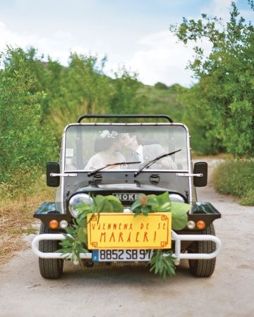 """This couple kissed in a rented Moke buggy with a hand-painted sign read """"Just Married"""" in French, the language of St. Barts"""
