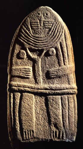 Statue menhir: Oval stone relief of woman with multiple necklaces, breasts, belt, holding a Y-shaped object in her hands