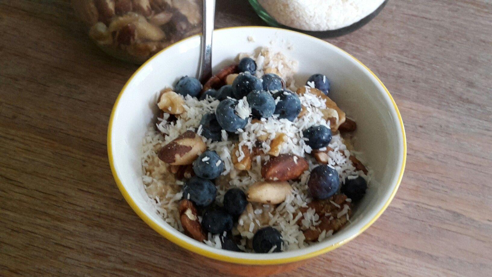 Havermout ontbijt met kurkuma, Gember met cacao nibs thee. Garneering van blauwe bessen, kokosschafsel, gemengde noten.