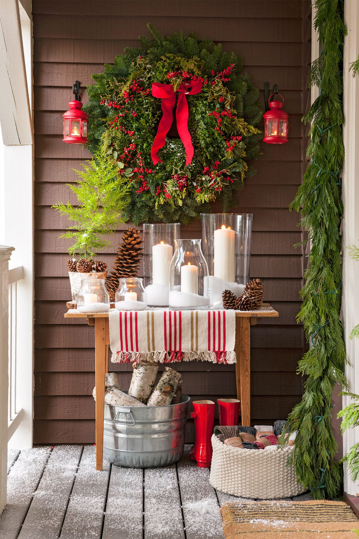 Make the most of sheltered porch corners with an impressive (and easy!) display of candles and greenery. This Christmas front porch display is so easy to recreate! #christmasdecor #outdoorholidaydecor #christmasoutdoordecor #porchdecorations #ideas #bhg