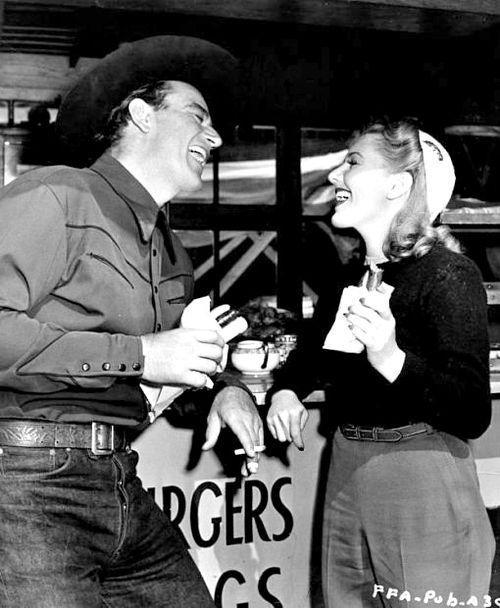 John Wayne and Jean Arthur taking a break on the set of A Lady Takes a Chance (1943).