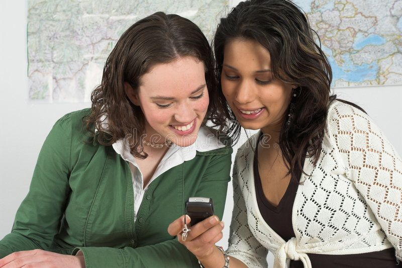 Checking out the latest sms. Girls reading a text message on a cellphone ,