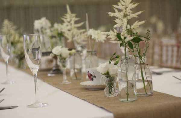 Long Tables With Hessian Runners And Bottles In Marquee. Country Style  Wedding Flowers At Hidcote
