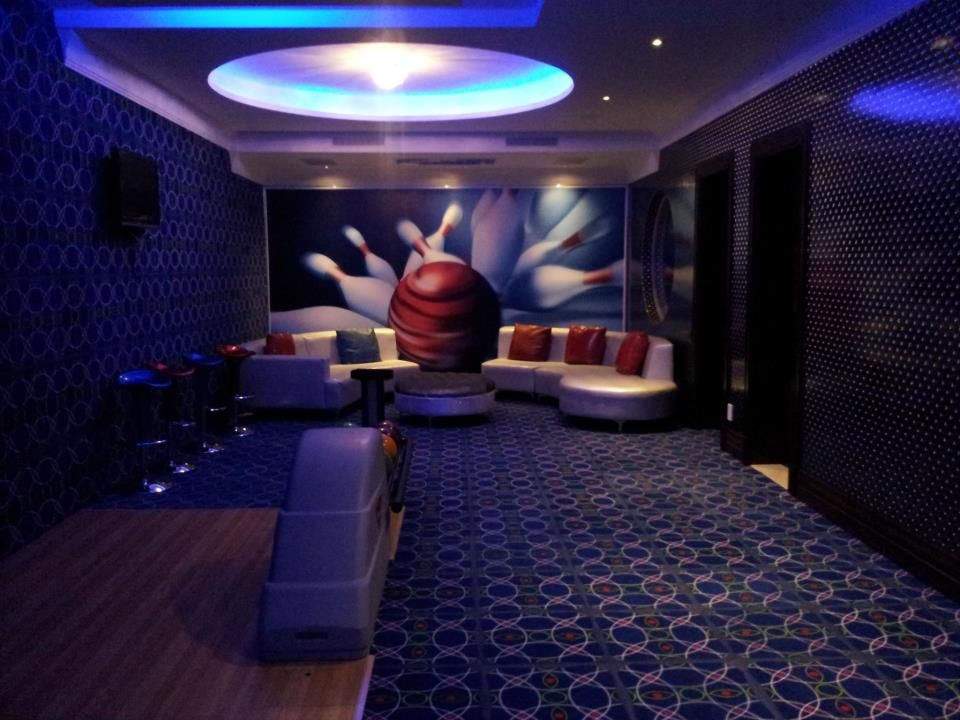 Seating area for home bowling alley with wall mural. in