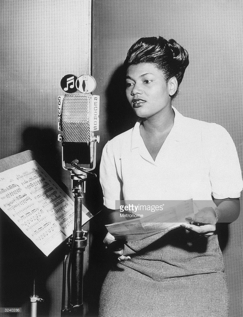 American pop singer Pearl Bailey stands at a microphone in a ...