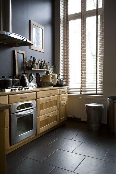 cuisine en bois naturel , mur noir , et carrelage noir- location de