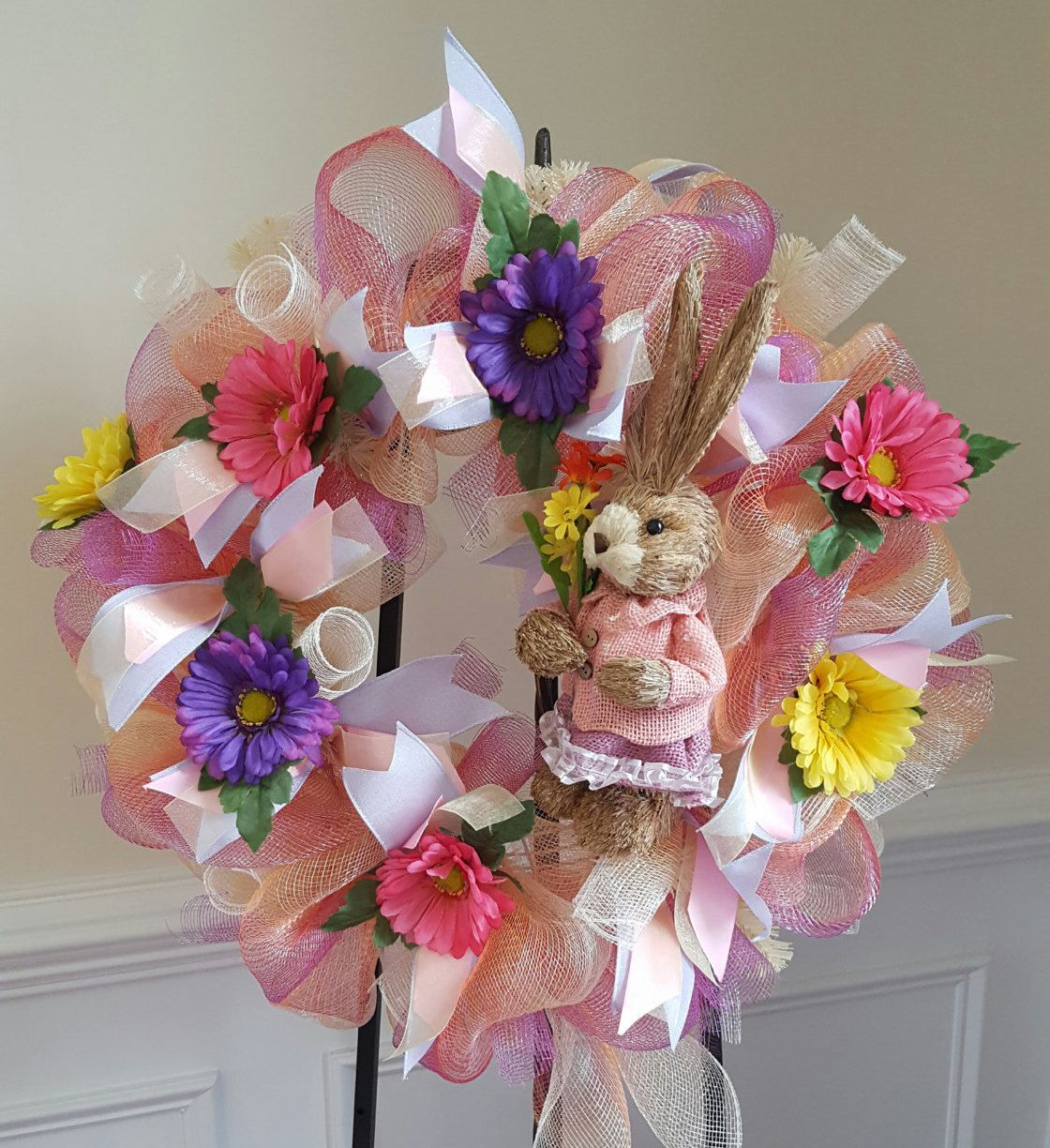 Spring wreath adorned by sisal bunny and pink, purple and yellow spring flowers