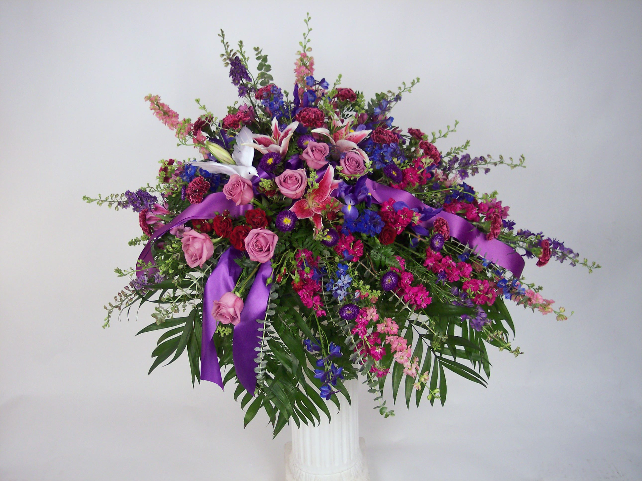 Remembrance gillespie florists indianapolis in casket spray is remembrance gillespie florists indianapolis in casket spray is filled with larkspur delphinium roses stock daisies a small dove and more flowers izmirmasajfo