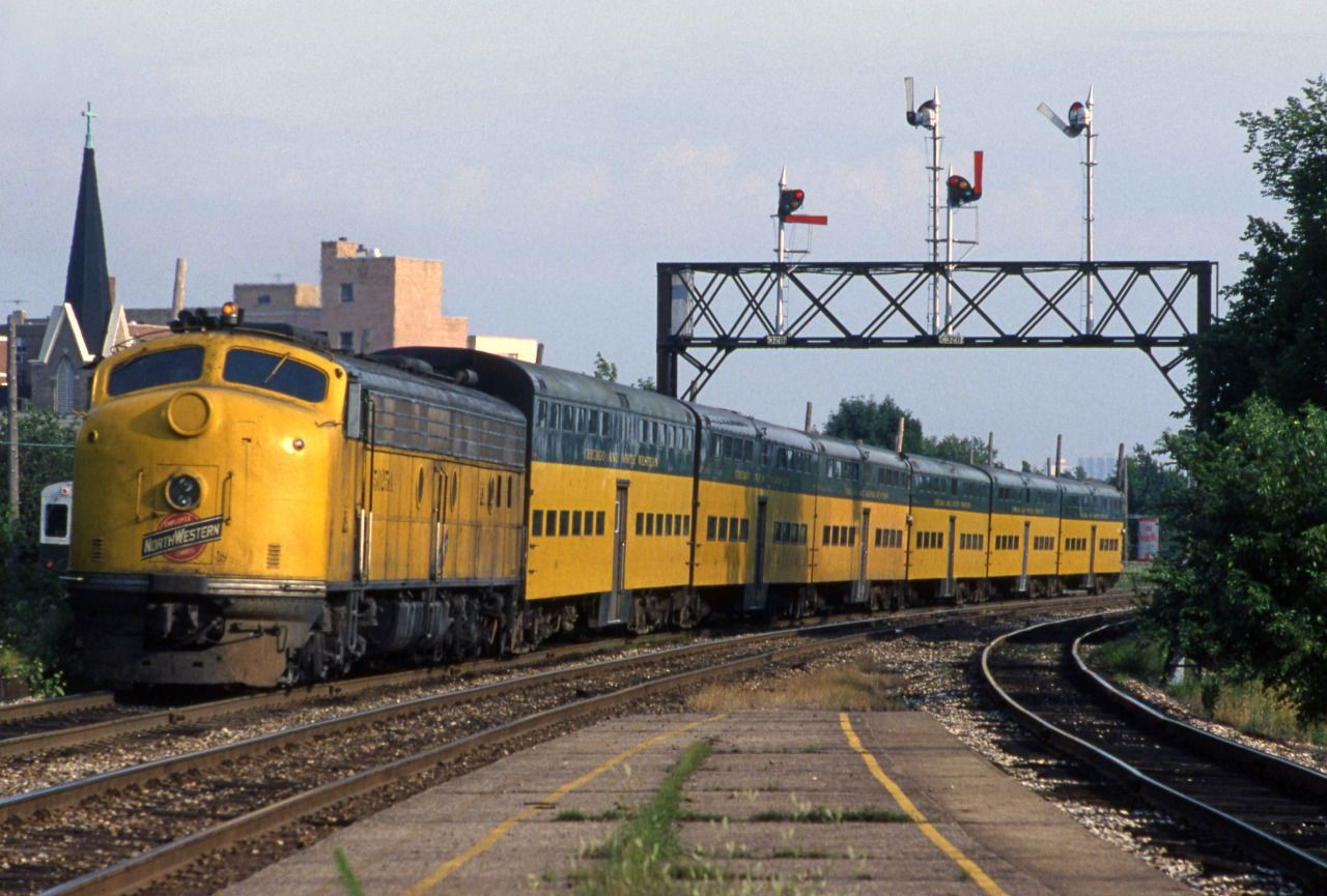 """Caption """"C&NW E8 5025A pushes her train away from Davis"""