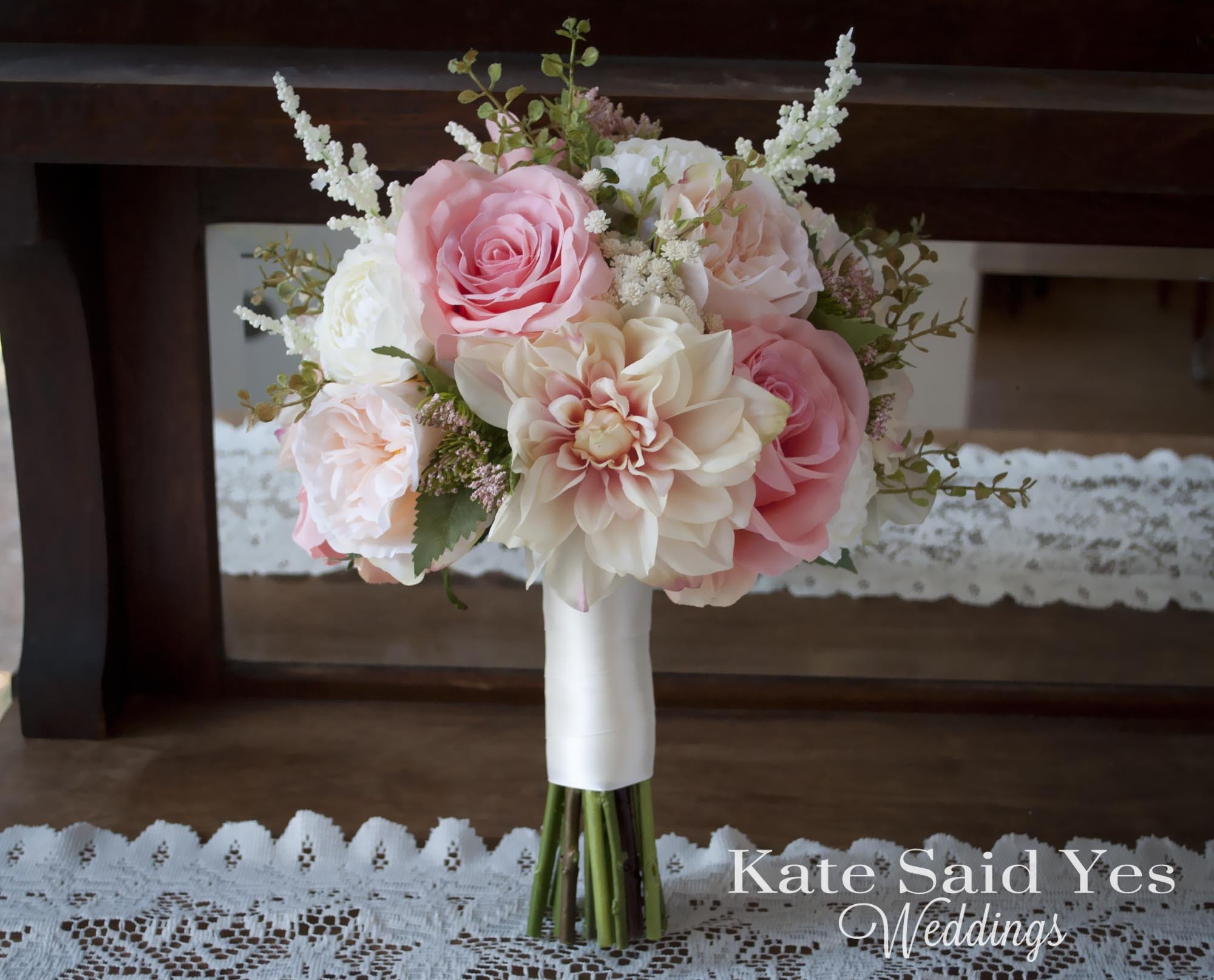 A beautifully romantic bouquet with a garden wedding feel. Blush pink and ivory dahlias, garden roses, and ranunculus are accented with astilbe and greenery. Th