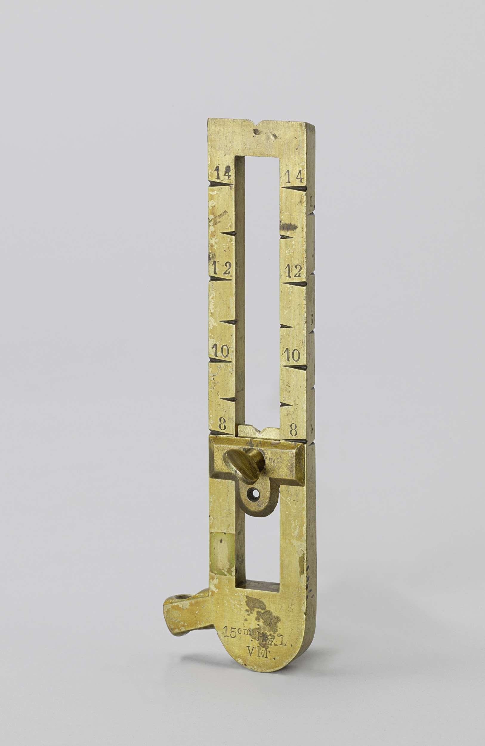 Anonymous   Opzet, Anonymous, c. 1860 - c. 1870   Messing opzet of vizier, bestaande uit twee verticale stangen waartussen een vizier op en neer schuift. Aan een kant hebben de stangen een schaal gaande van 8 tot 14; aan de zijkant is een schaal aangebracht van 4 tot 8. Het vizier heeft een ronde voet met een horizontale nok; oorspronkelijk was aan het vizier ook een ketting bevestigd, waarmee het aan het affuit werd gekoppeld. Dit vizier was voor veldgeschut; het opschrift slaat op een 15…