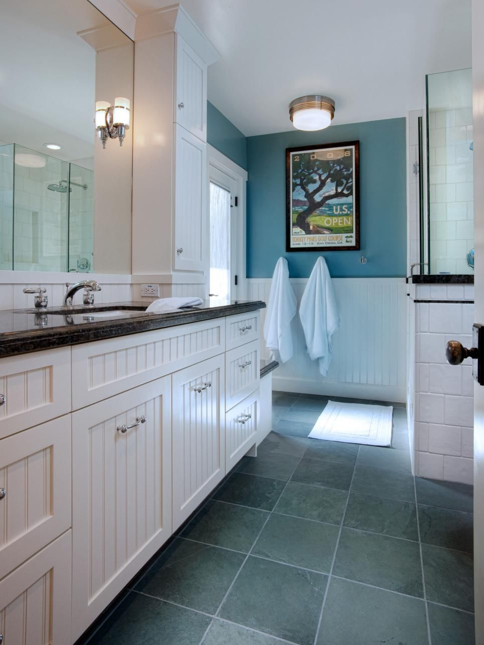 This charming bathroom features white beadboard cabinetry contrasted ...