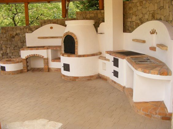 Photo of Compact outdoor kitchen with fireplace for kettle, pizza oven, grill and door …