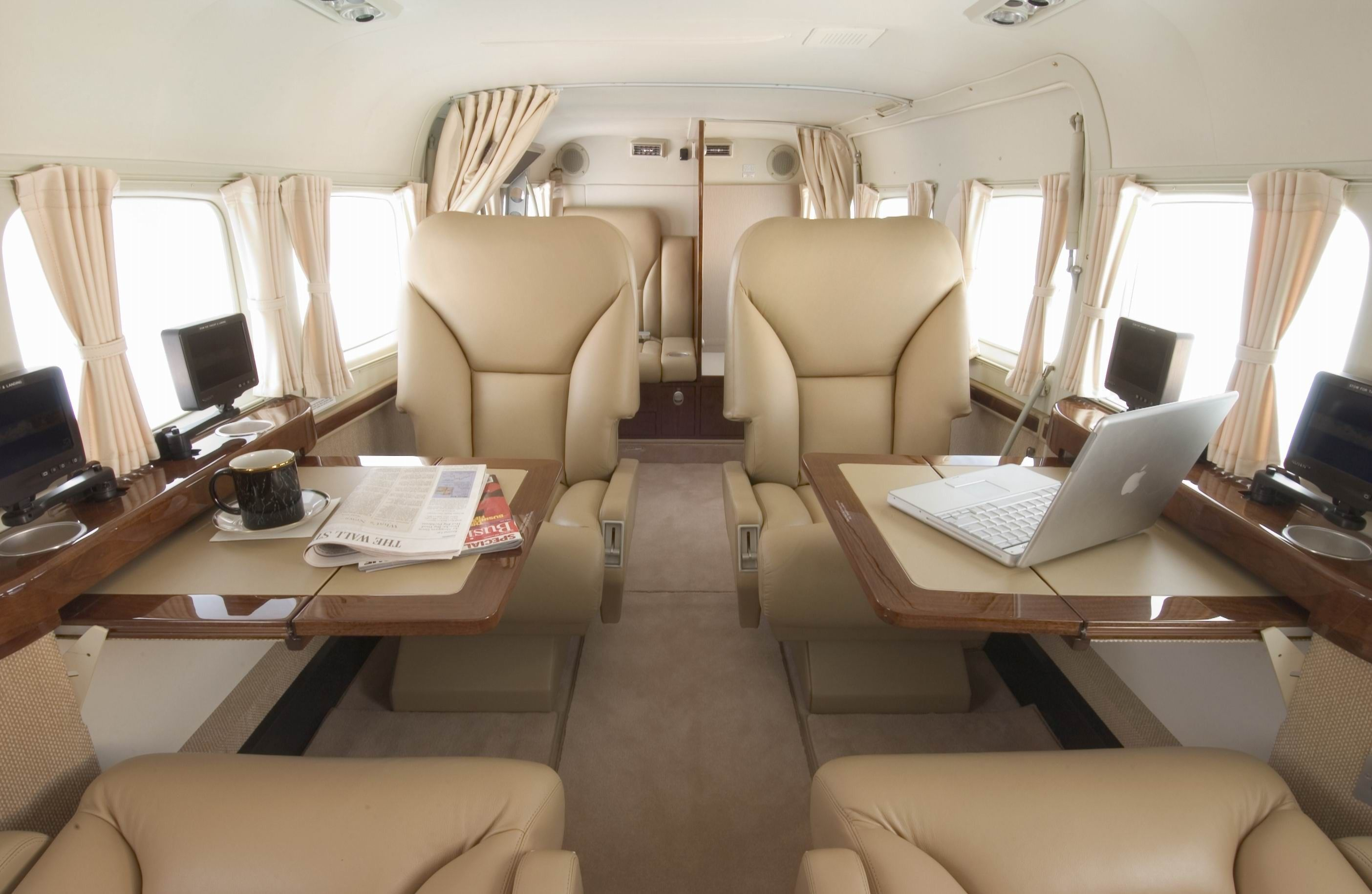 Private jet interior furnished like a vintage train aviation - Luxury Aircraft Solutions Cessna Caravan Available For Charter
