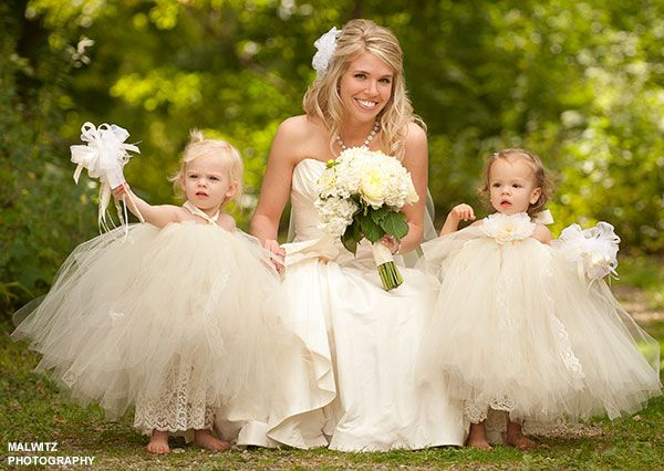 Bride poses with two toddler flower girls in matching for Matching wedding and flower girl dresses