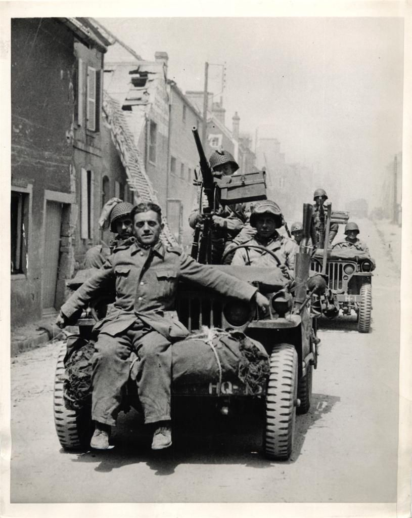 1944- German sniper, captured in St. Mere Eglise, rides off to captivity on the front bumper of a jeep.