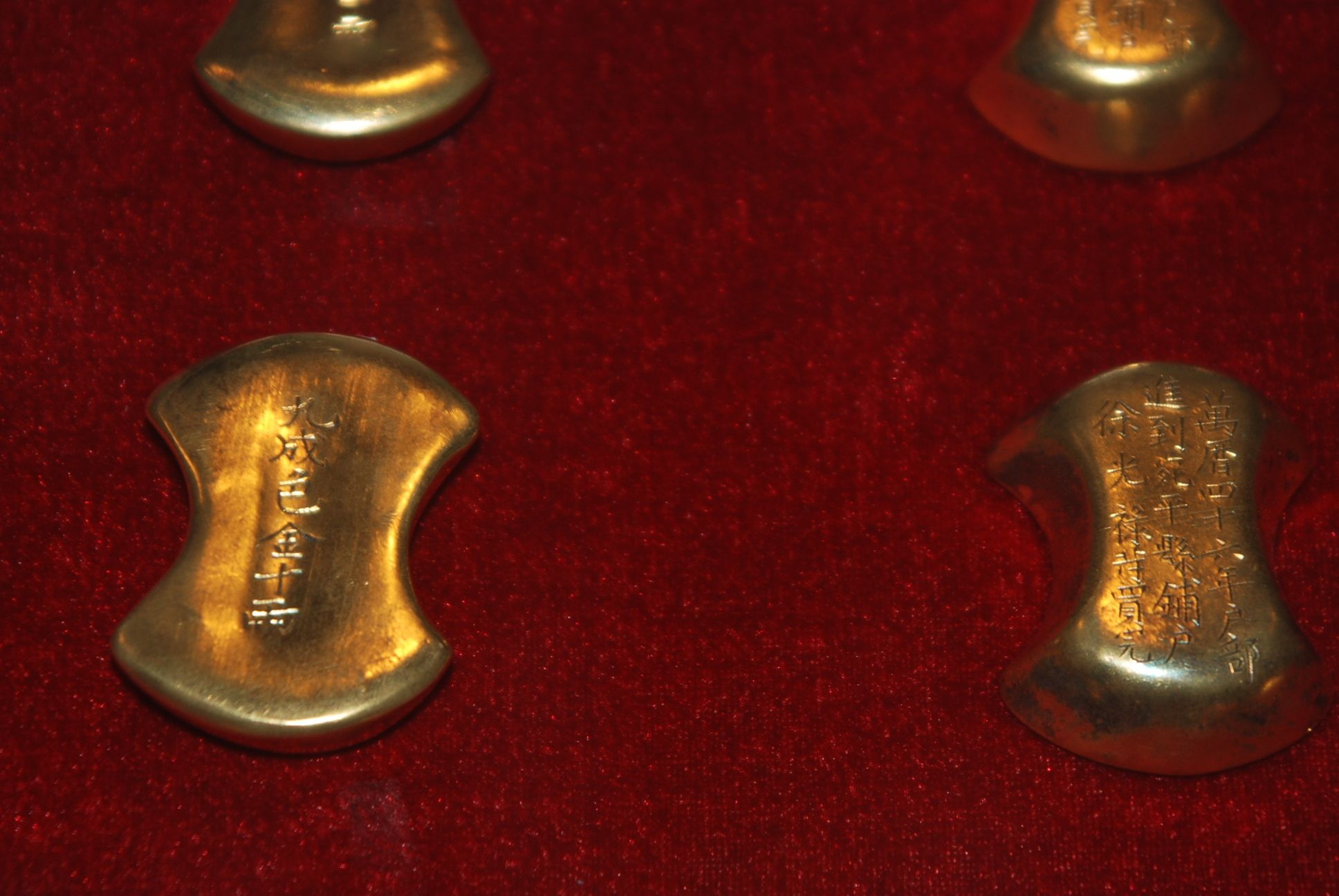 Zoom in of the front (left) and back sides (right) of two of the gold ingots in the collection.