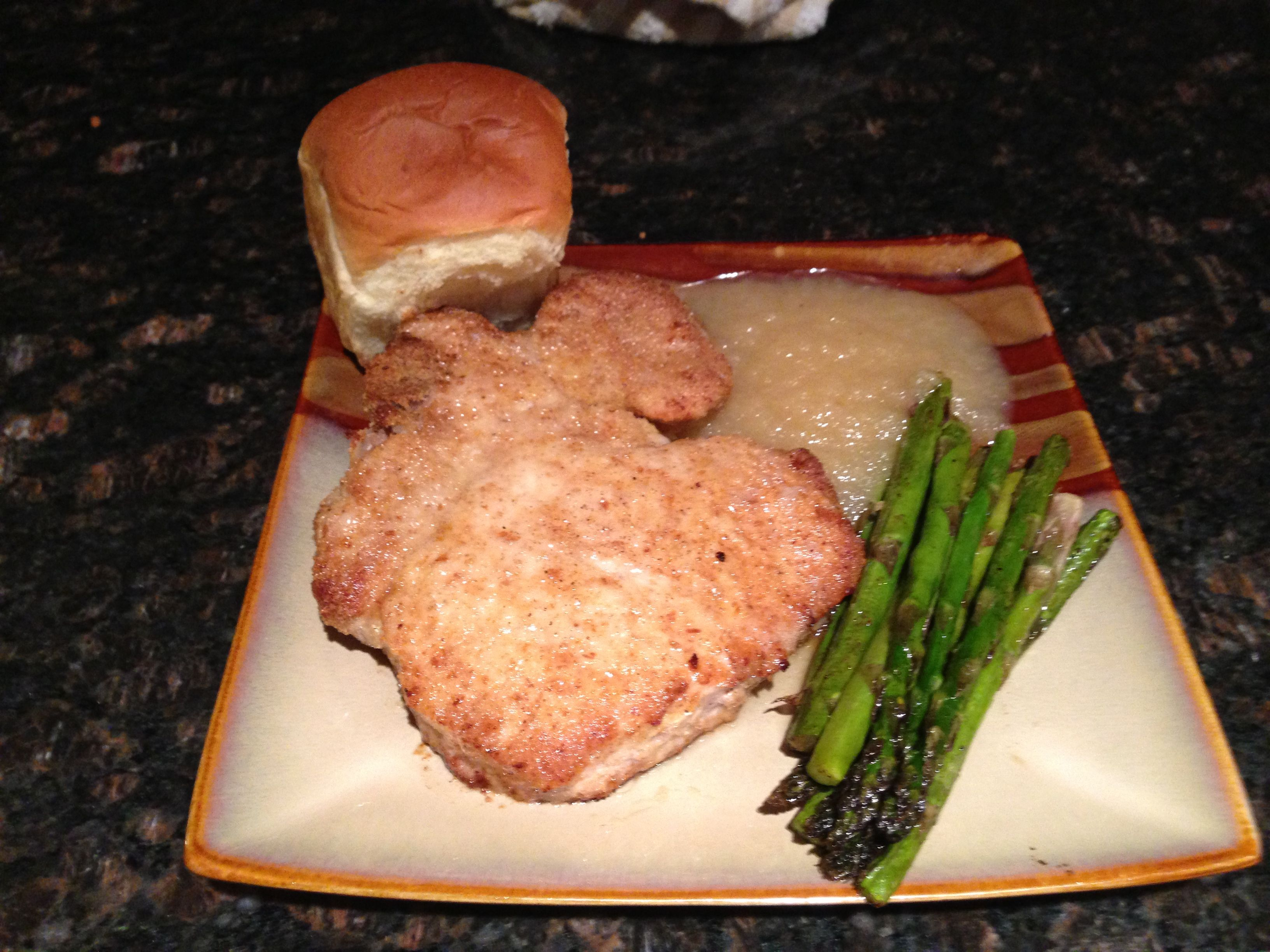 Oven fried pork chop with roasted asparagus, Hawaiian roll, and apple sauce