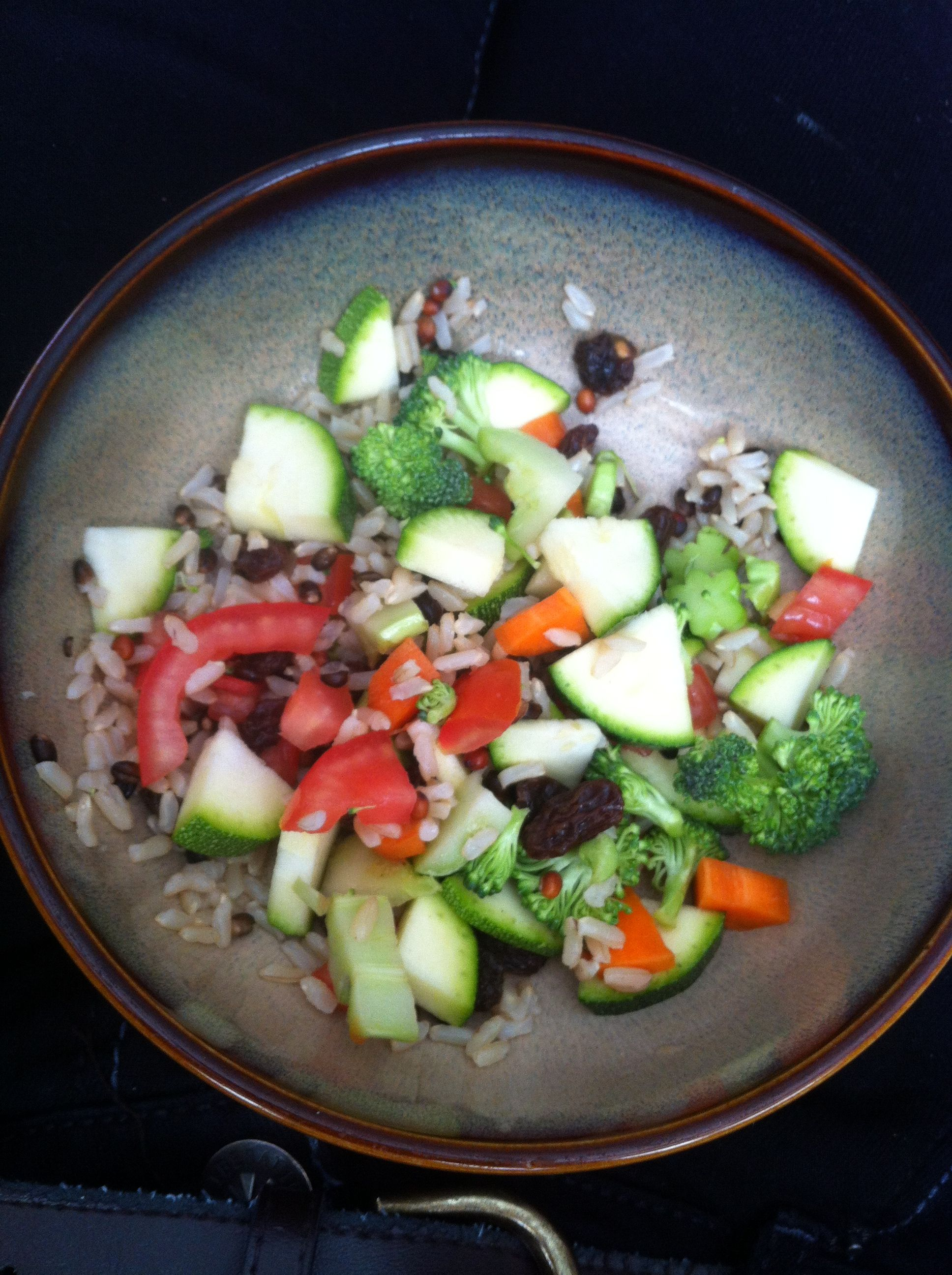 Cut zucchini, tomato, broccoli, carrots, and raisins on a bed of brown organic rice...yummmmy linner for me lol