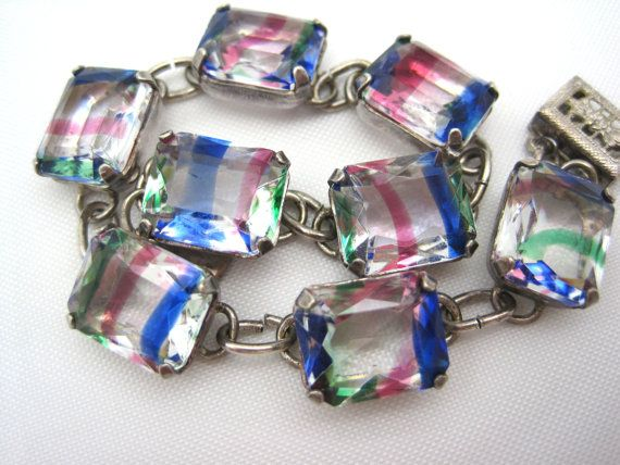 A stunning Art Deco bracelet. It features iris glass stones set in sterling silver. Iris glass is clear glass with a sort of rainbow of stripes