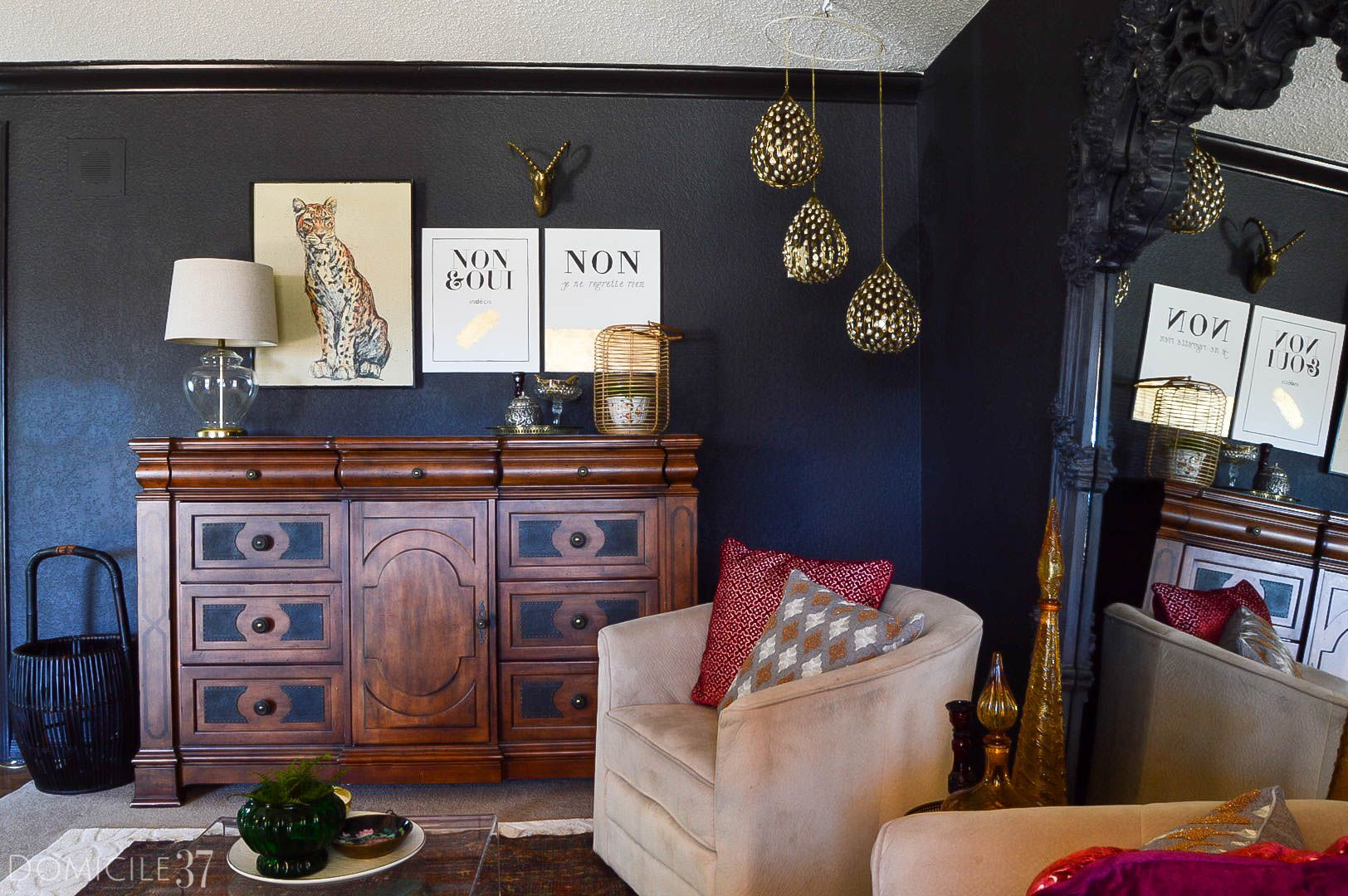 Vintage Eclectic Sitting room inspired by Moroccan decor   Layered persian rugs   Dresser console on black wall with chic art   vintage art   acrylic coffee table with swivel chairs
