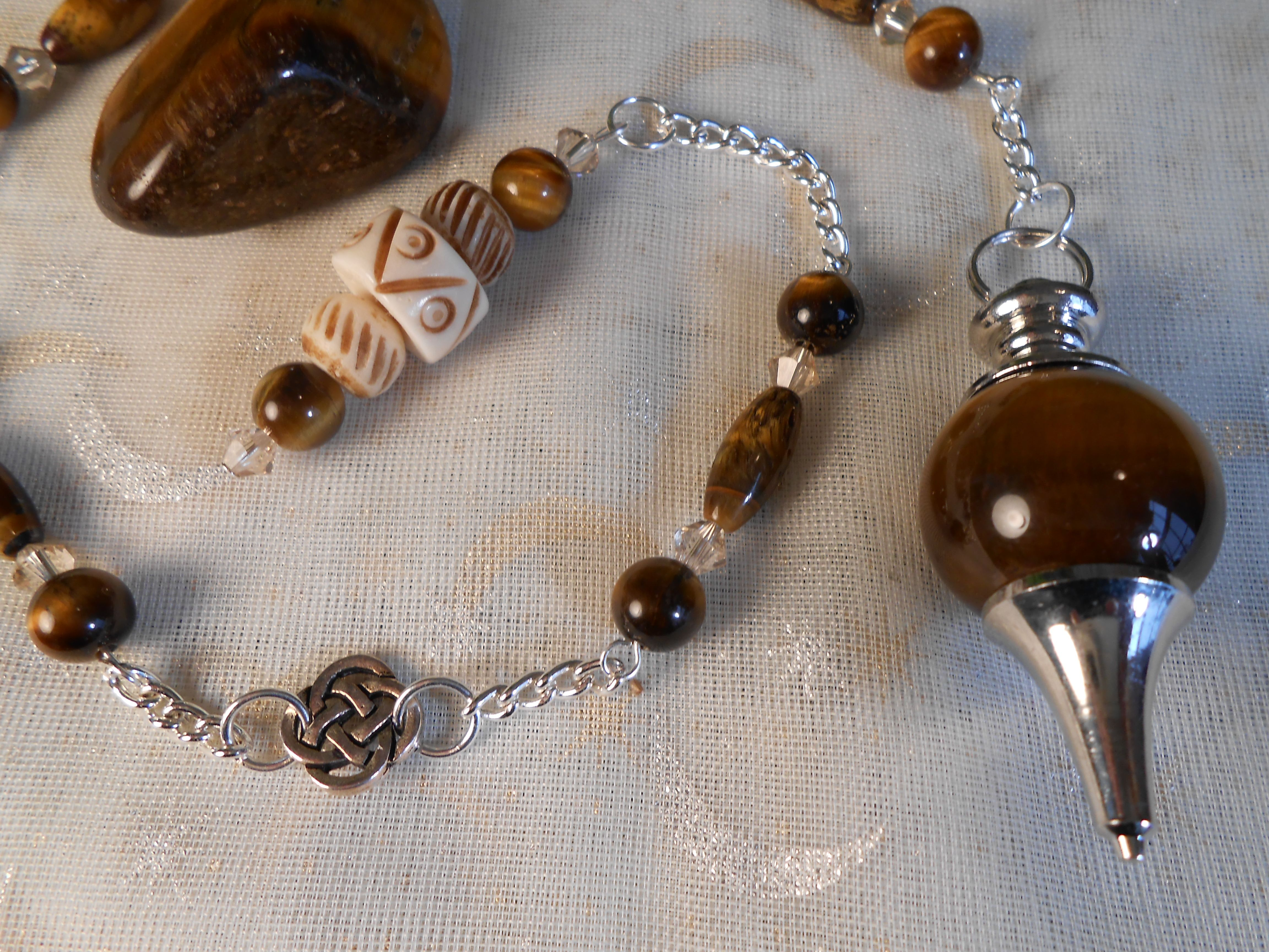 "15"" Tiger Eye/Carved Bone Divination & Healing Pendulum.  Silver celtic knot and topaz swarovski beading.  $20.00"