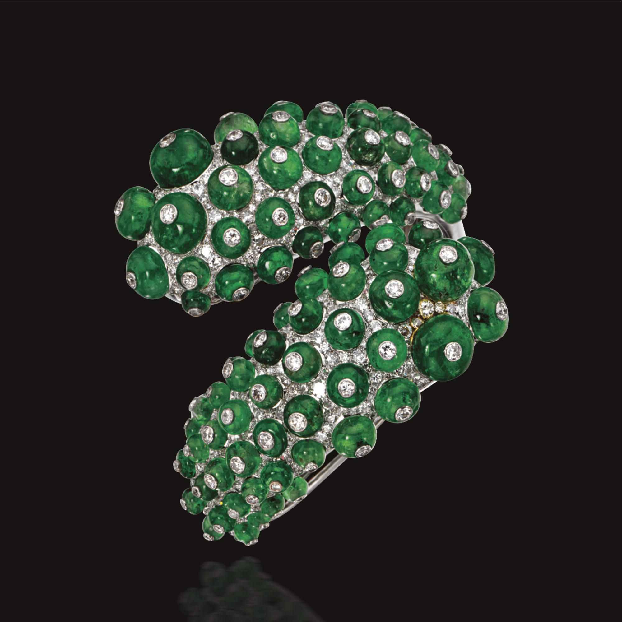 EMERALD BEAD AND DIAMOND BANGLE-BRACELET, PAUL FLATO, CIRCA 1940 Of hinged crossover design, the lobed bombé terminals studded with numerous emerald beads within a ground of pavé-set diamonds, each bead inset with a small round diamond, mounted in white gold