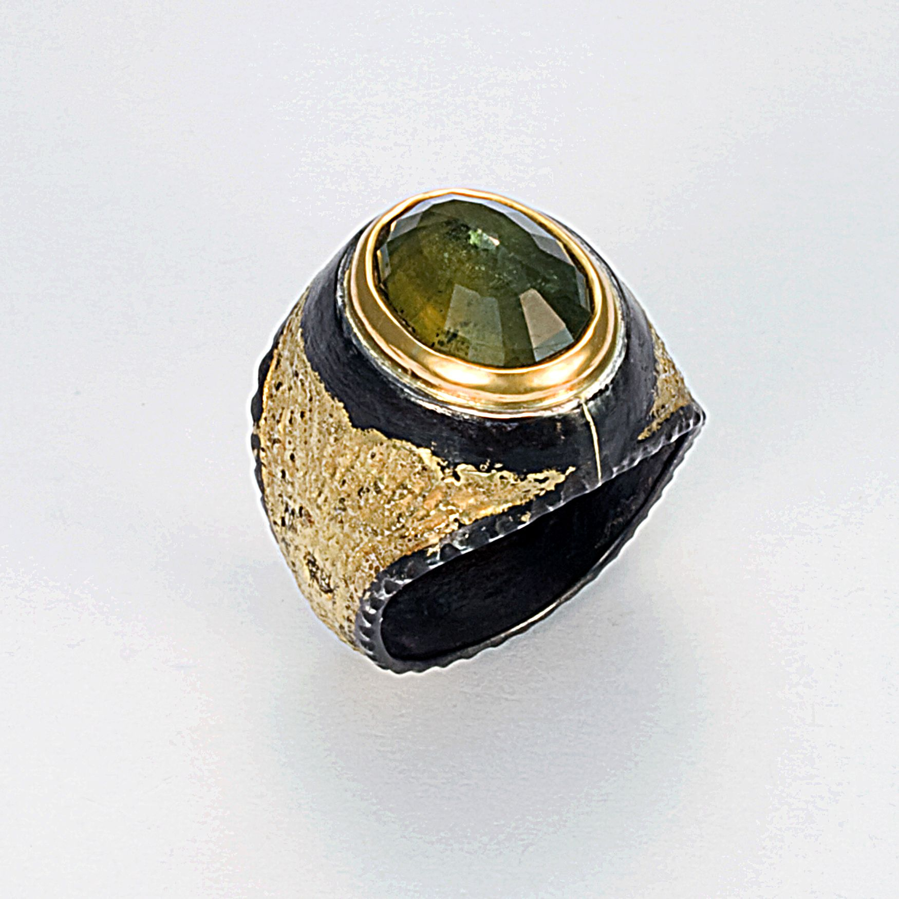 Hand textured iron, fused with 20karat gold.  5.84 ct. green sapphire set in 22karat gold.  Obscure art deco patina.