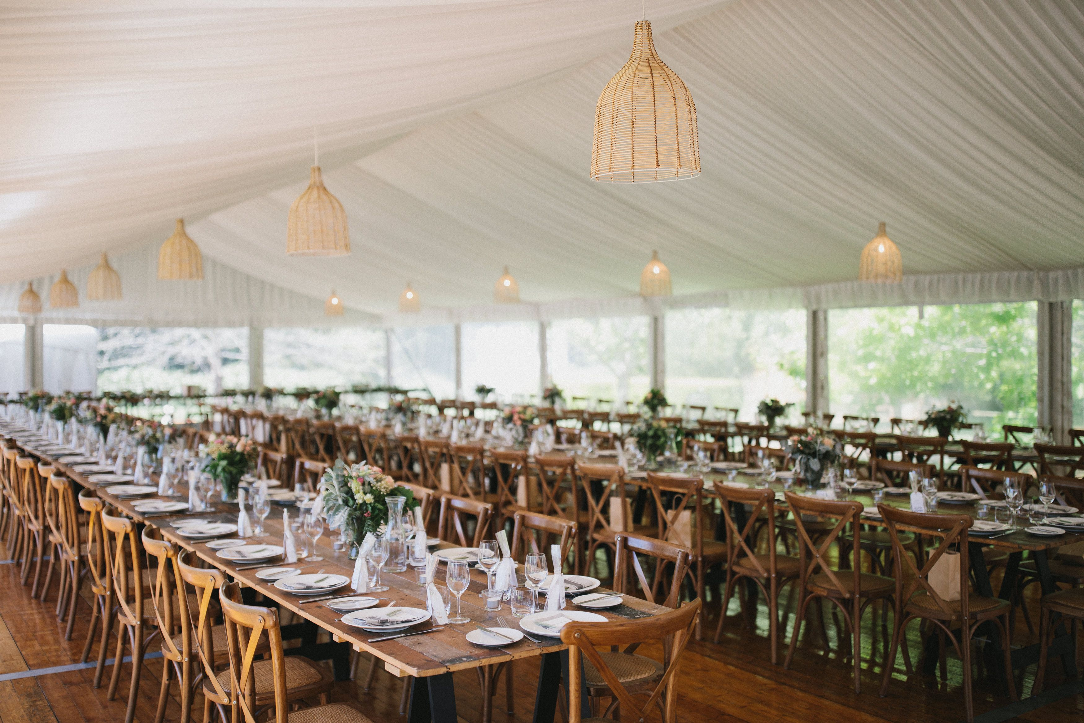Vintage timber trestle tables timber cross back chairs silk lining rattan lampshades clear walls integrated timber flooring south coast weddings